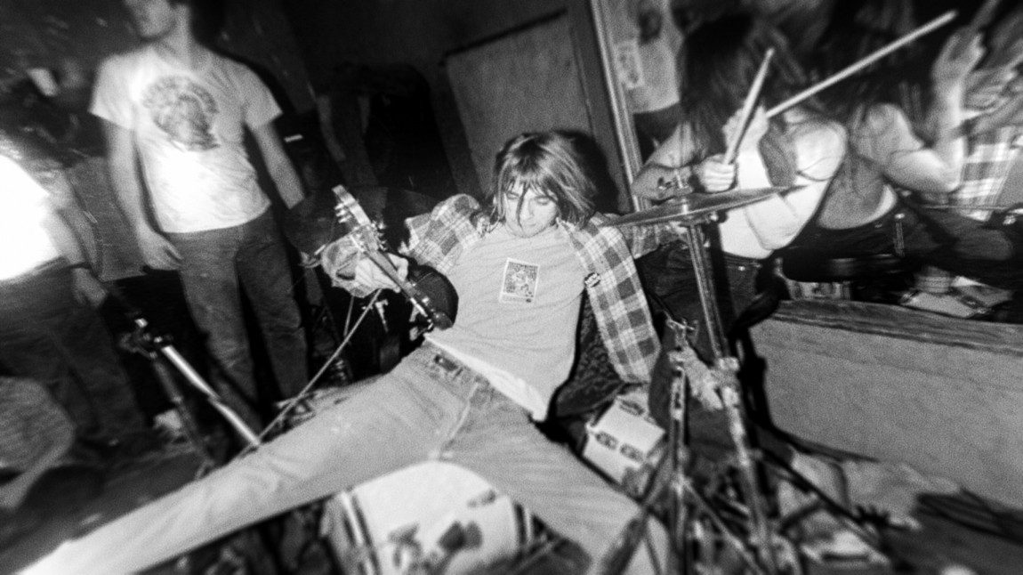 Kurt Cobain sittende på et trommesett under en av Nirvanas tidlige konserter. (Foto: Arts Alliance, End of Movie, LLC)