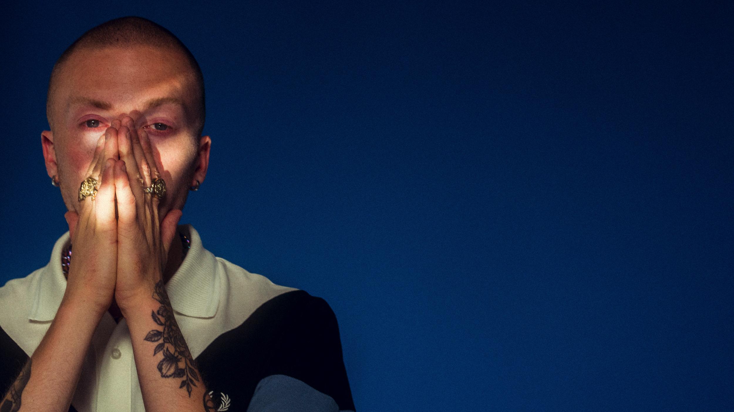 Martin Hazy står med blå bakgrunn og ser i kamera medan han delvis dekker for ansiktet med hendene.