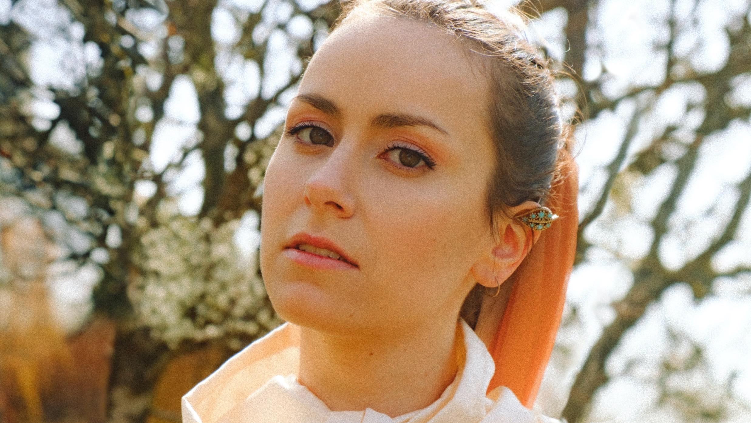 Nærbilde av artisten Iris, som står utandørs og ser i kamera.