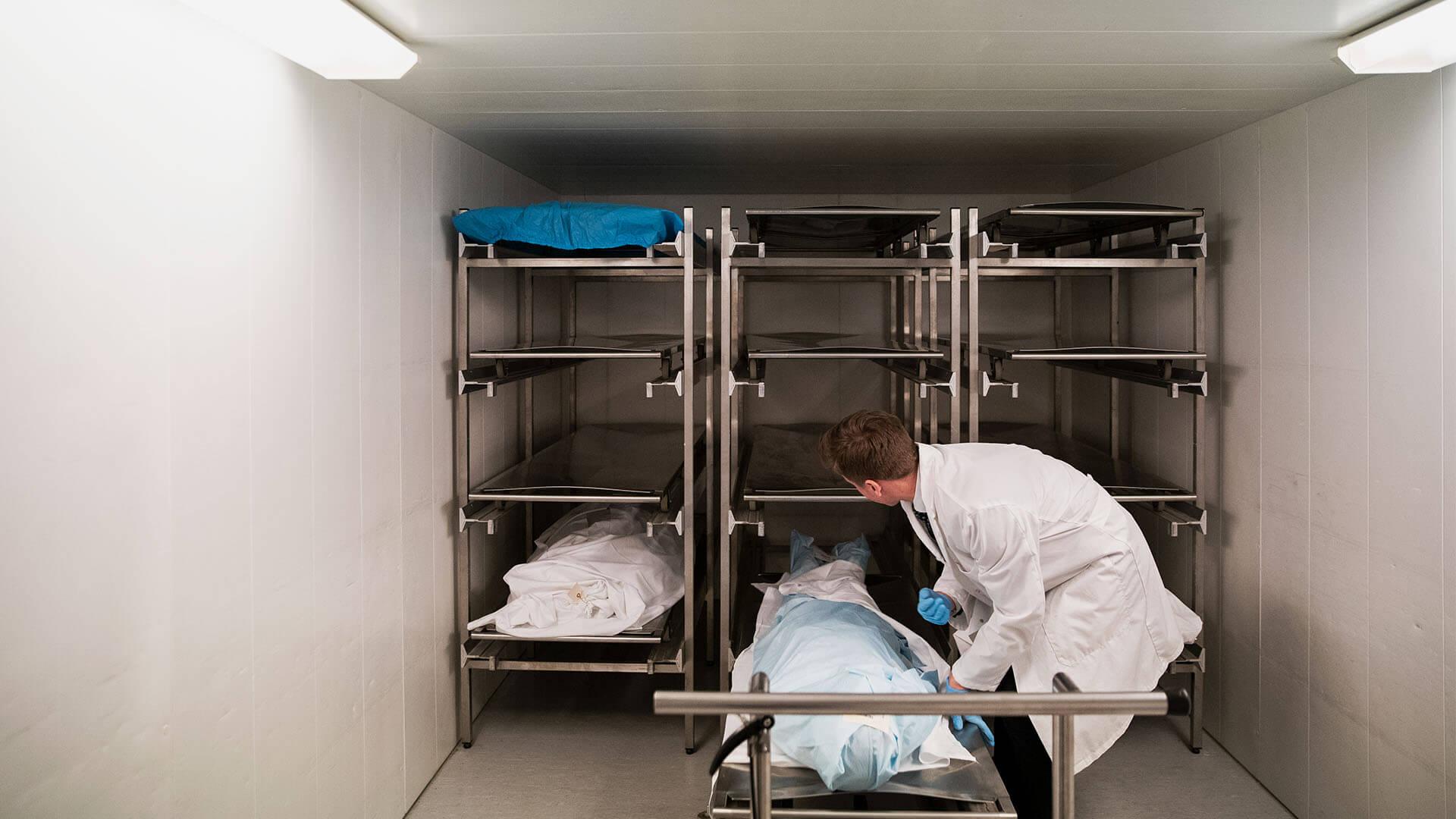 Kristian bøyer seg ned mot midten av en metallhylle inne i et hvitt kjølelager, og drar ut den nederste hylla hvor en kropp er pakket inn i hvitt og lyseblått materiale.