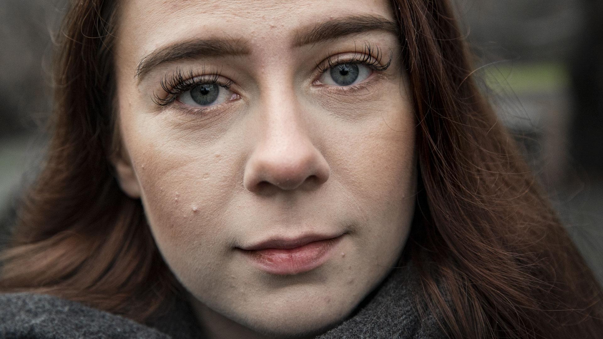 Bildet er et nærportrett av Synne, så ansiktet dekker hele bildeflaten. Synne ser inn i kameraet med mørkeblå øyne. Hun har brunt, gyldent hår som blåser litt bakover mot skuldrene. Vippene er lange, og huden lys. Munnen er lukket, og ansiktsuttrykket er en krysning av alvorlig og smilende. Rundt halsen har hun et grått skjerf.