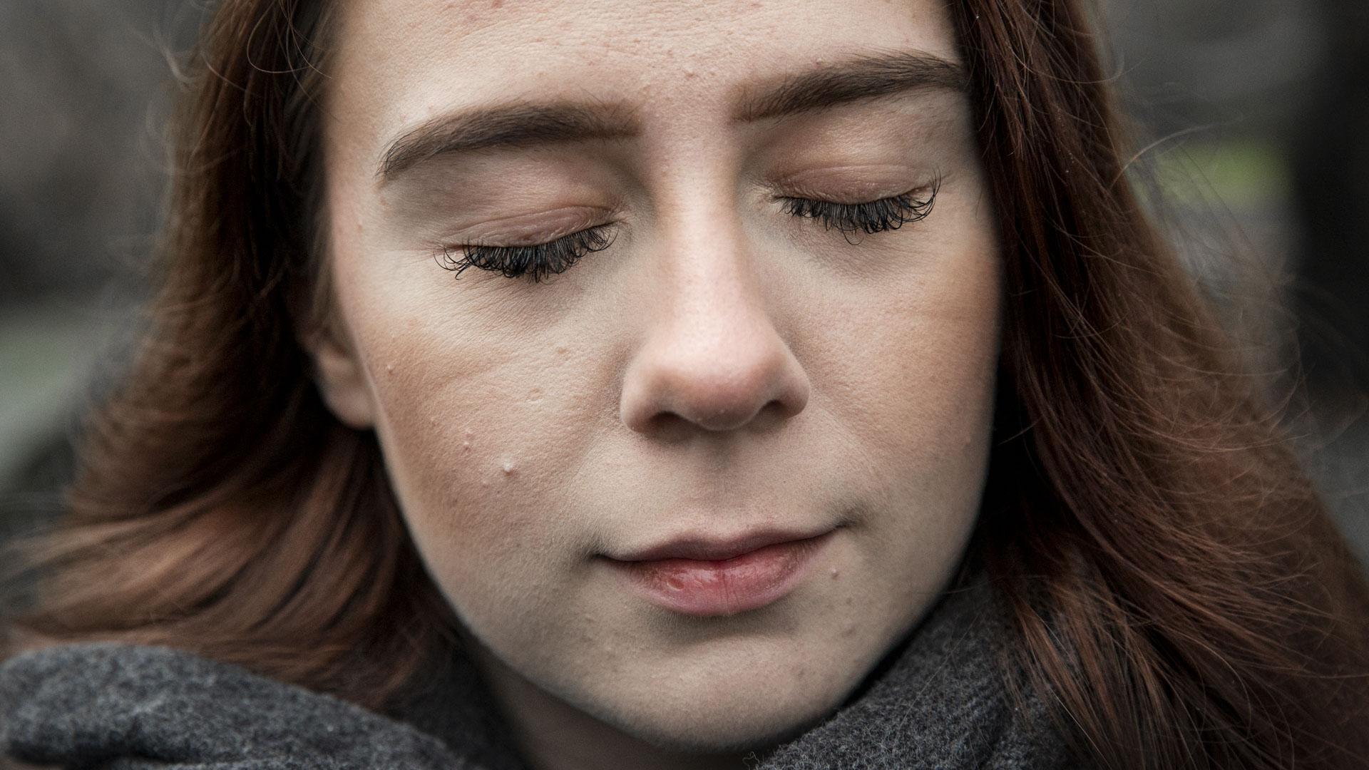 Bildet er et nærportrett av Synne, så ansiktet dekker hele bildeflaten. Synne har øyne lukket, så hun ser tenkende ut. Hun har brunt, gyldent hår som blåser litt bakover mot skuldrene. Vippene er lange, og huden lys. Munnen er lukket, og ansiktsuttrykket er en krysning av alvorlig og smilende. Rundt halsen har hun et grått skjerf.
