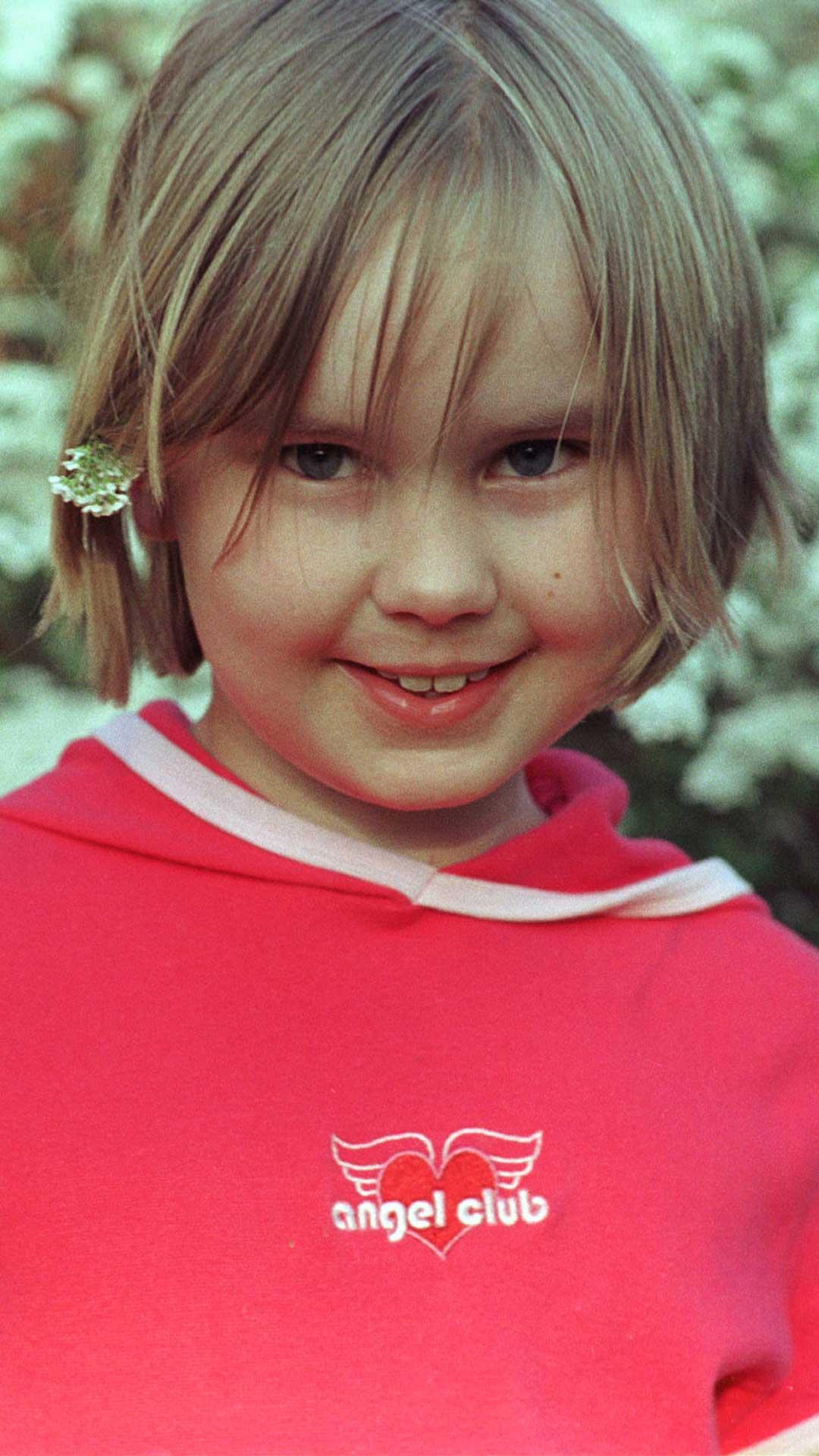 En jentunge med brunt hår, pannelugg, brune øyne, fyldig fjes og lurt smil ser rett i kameraet. Bak øret har hun en hvit blomst. På seg har hun en knall rosa T-skjorte hvor det står «Angel Club» i hvit skrift med vinger bak seg. Bak henne er grønne busker med hvite blomster.