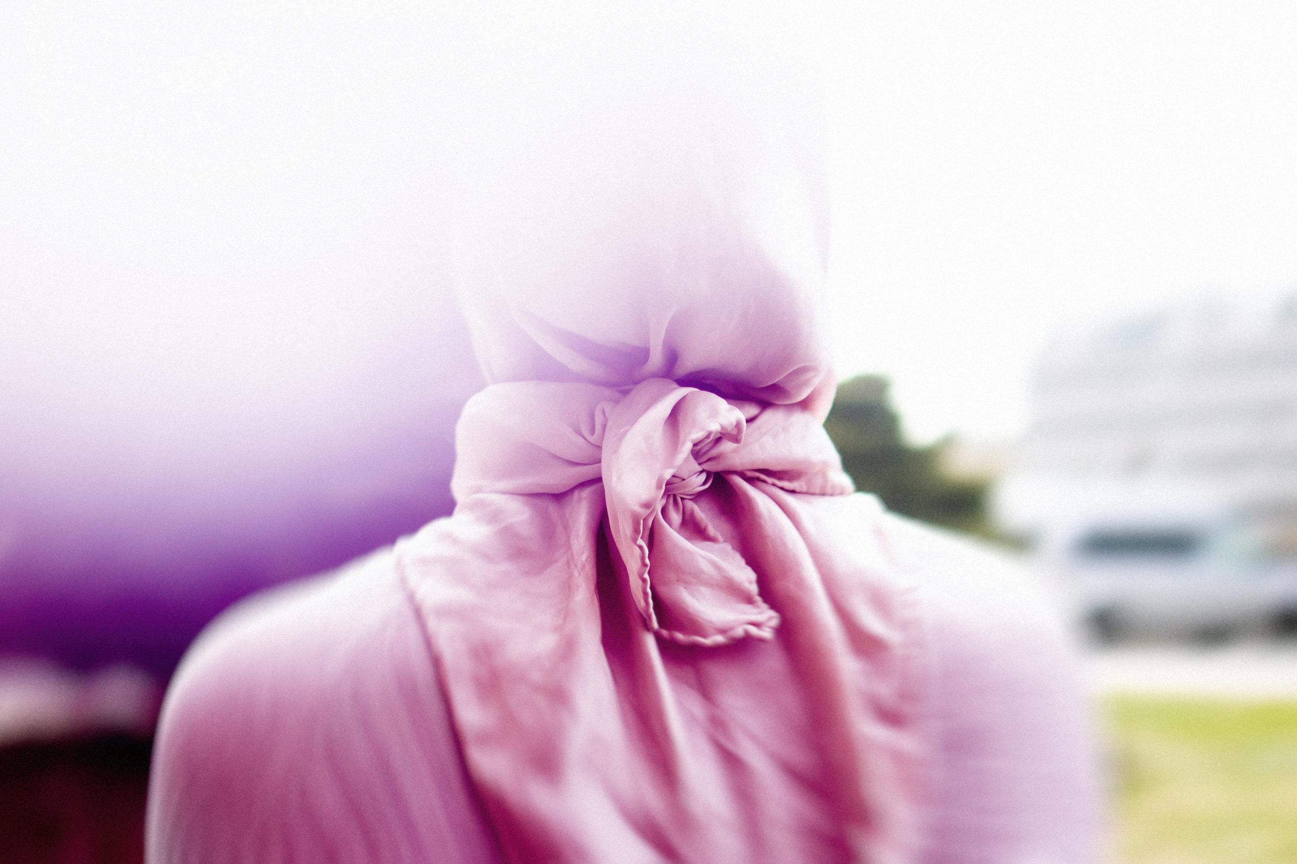 En kvinne sitter med ryggen mot kamera. Hun har på seg en hijab som skjuler håret. Bildet skal være anonymt, og det er lagt på et rosa skjær i fotografiet for å skjule identiteten og klesfargene til personen på bildet.
