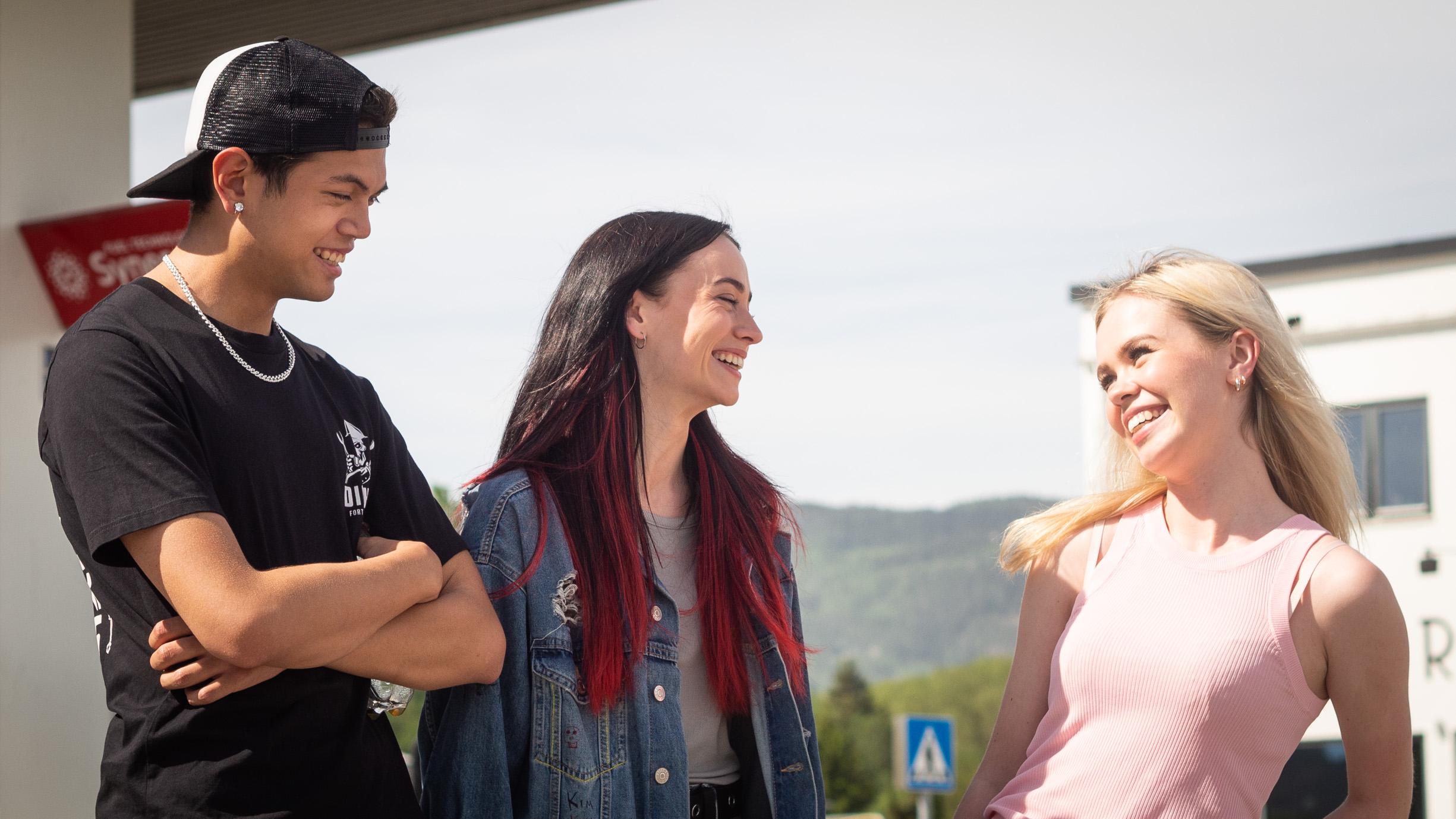 Et bilde av «Kim» (Matthew Santos) og Maja Christiansen (25), som spiller «Hege» i serien. De står på en bensinstasjon. De ser mot Amalie Sporsheim (20) spiller datteren til ordføreren, «Malene».