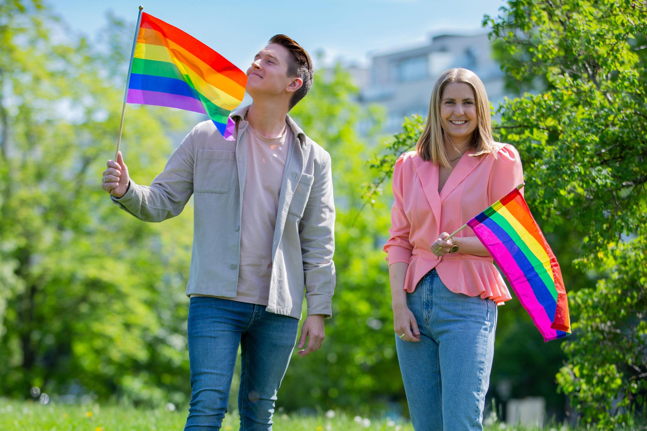 Benjamin har på seg en lys jakke og rosa t-skjorte. Han har et prideflagg i hånden og ser mot flagget. Han har på seg blå jeans. Silje har på seg rosa bluse og holder et prideflagg i hånden. Hun har et stort smil og ser rett inn i kamera. Hun har lys blondt hår. Hun har på seg blå jeans. De står foran grønne trær.