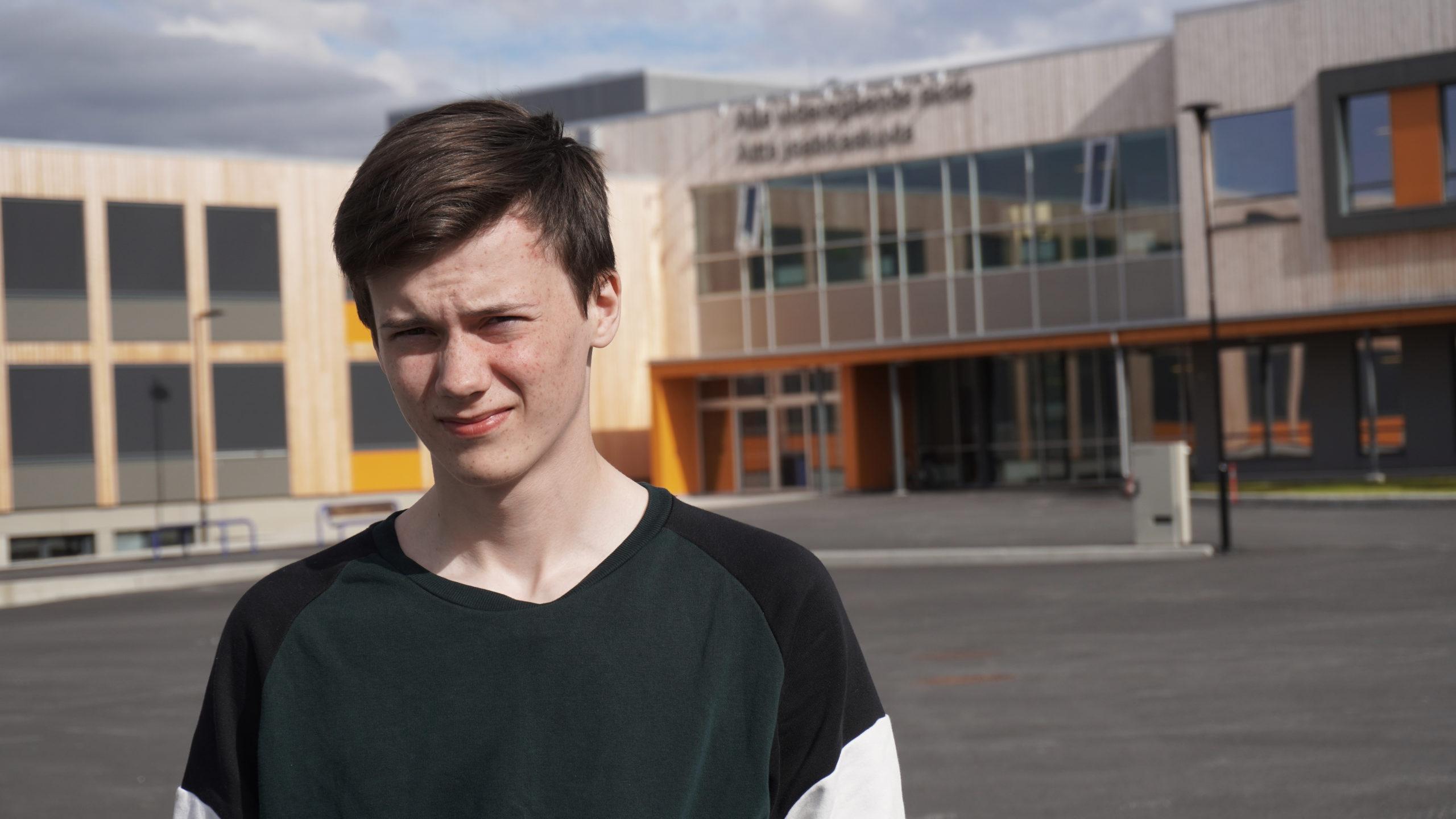 En ung gutt, rundt slutten av tenårene, med fregner i ansiktet, mørkt hår og lys hud kikker bekymret mot kamera. Leif-Ove som han heter, ser brydd ut. Bildet er tatt i halvprofil foran en skurrete Alta Videregående skole.