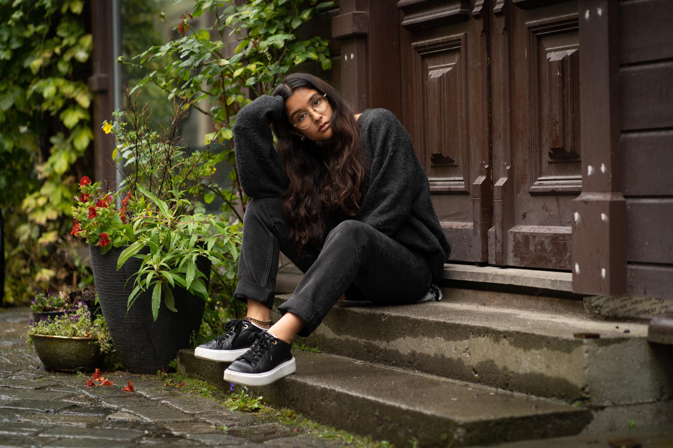 En ung mørkhåret jente sitter i en trapp. Jenta ser seriøst inn i kameraet. Hodet er på skakke, og ligger i håndflaten til høyrehånd. Høyrehånd er plantet i kneet. Hun har på mørke klær, og mørke sko. Bak hun er det planter.